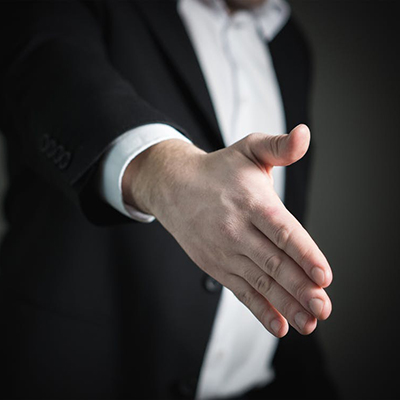 Person reaching out to shake hands and congratulate