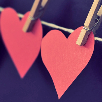 construction paper hearts held to a twine line with wooden paperclips