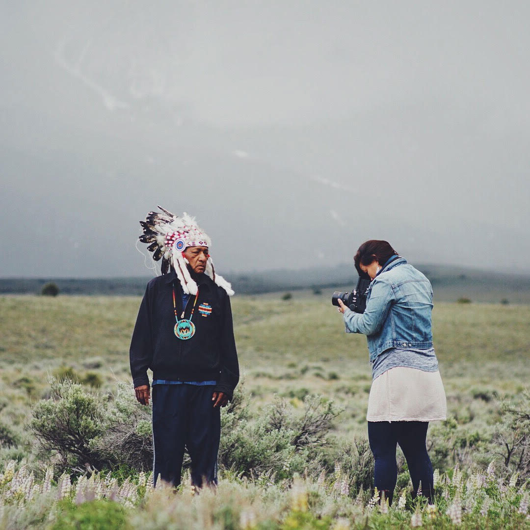 Matika Wilbur in a field at the foot of a mountain range taking a photograph of a native american man in full headdress