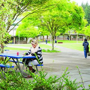 Photo of student sitting at a picnic table in the courtyard.